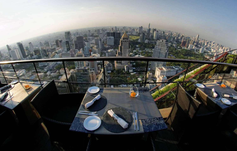 Tafeltje met twee stoelen met uitzicht over de sky line van Bangkok