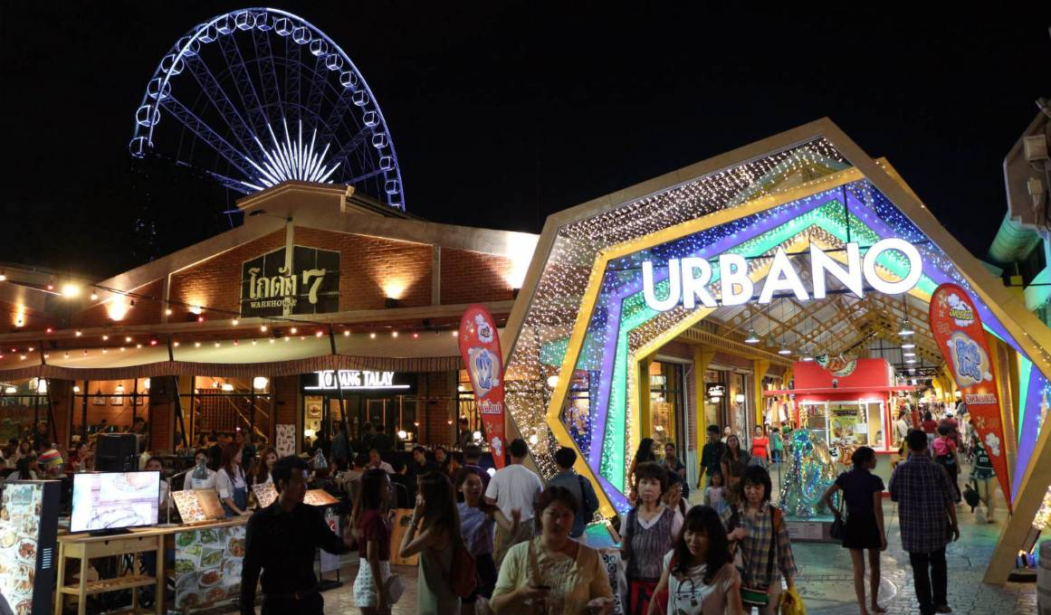 Urbano en het reuzenrad op de achtegrond tijdens de avond op ASIATIQUE The Riverfront in Bangkok, Thailand
