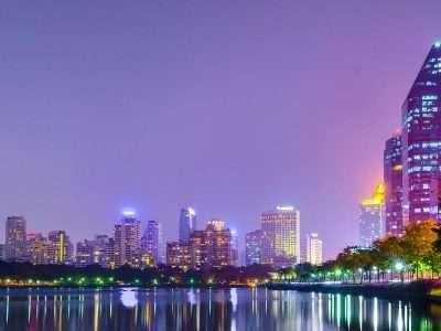 Het Benjakiti Park Tijdens De Avond In Bangkok. Je Ziet Overal Lichtjes Van De Omliggende Hoogbouw