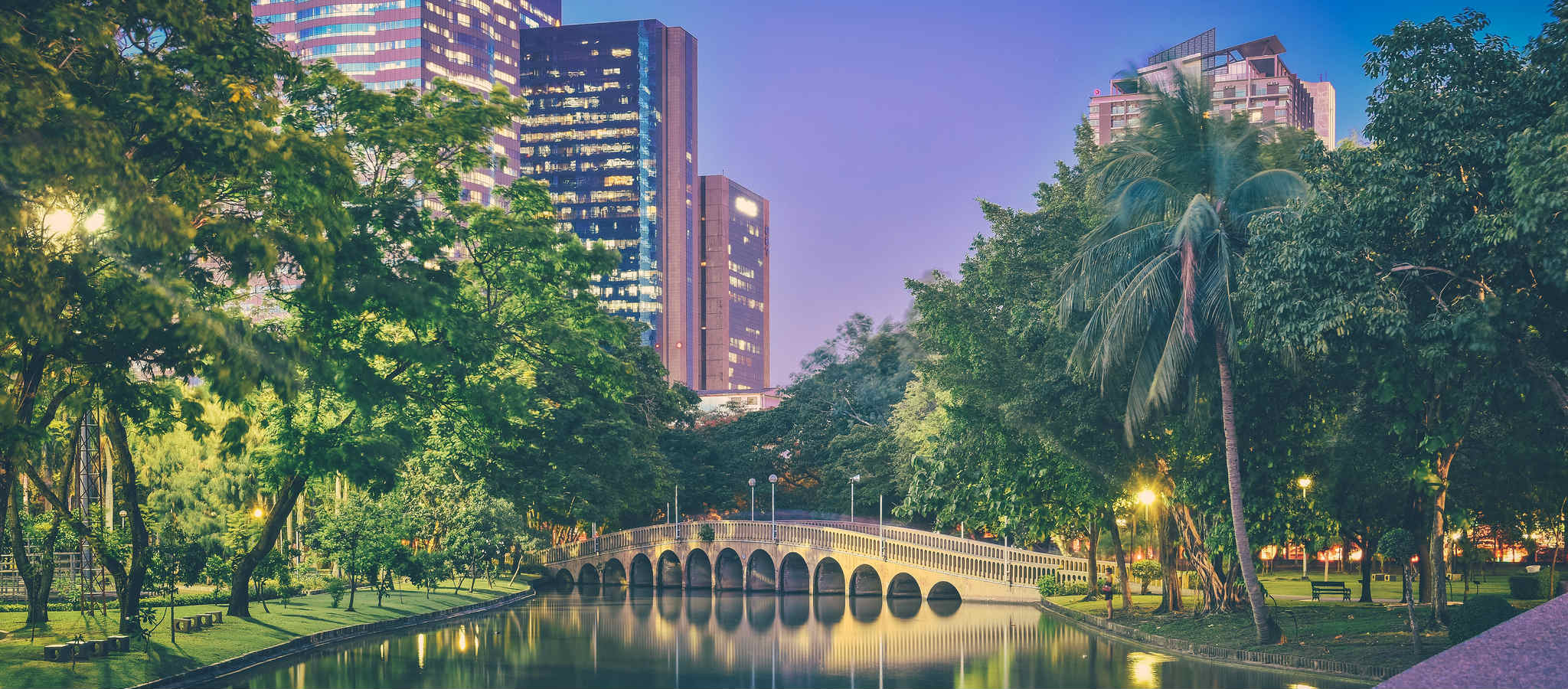 A bridge and high buildings in the background at Chatuchak Park in Bangkok