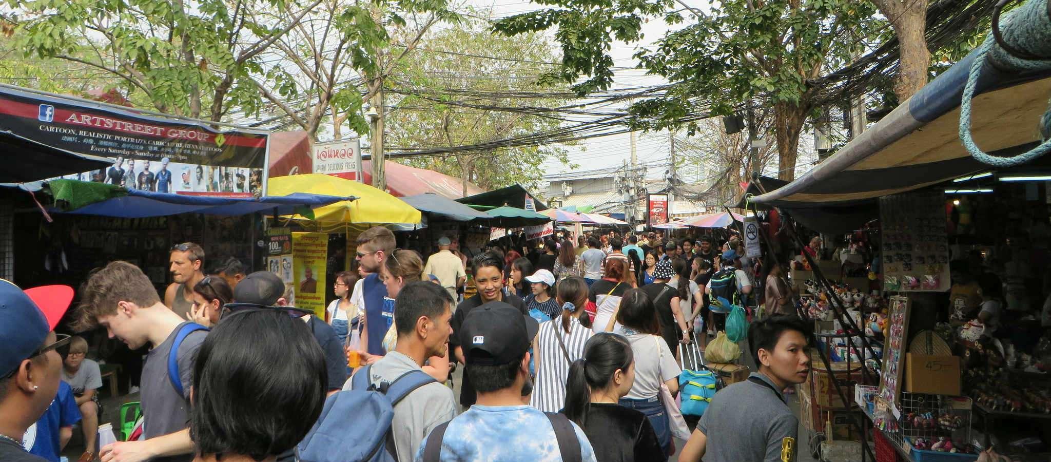 Vee mensen tussen de marktkramen van de Chatuchak Weekend Market