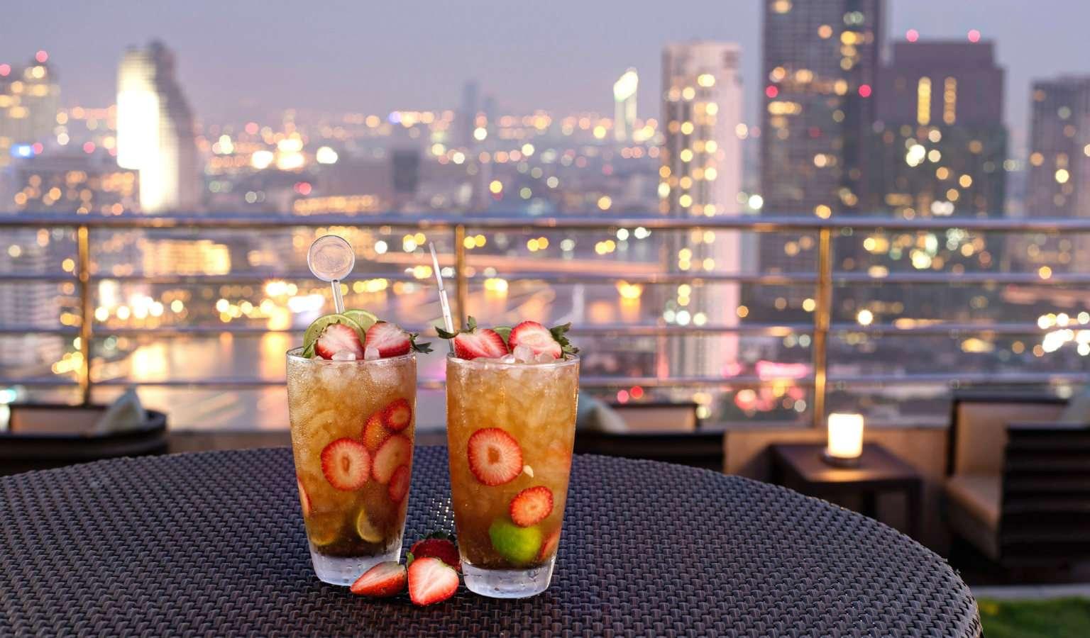 2 Cocktail's met aardbeien garnering op een tafeltje, met op de achtergrond de skyline van Bangkok
