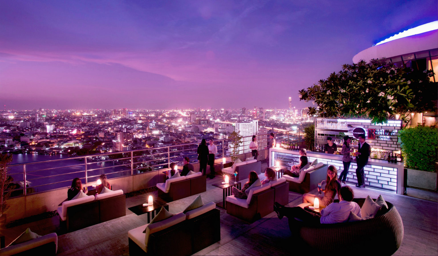 Mensen op lounge van de Three Sixty Sky Bar met uitzicht op de rivier