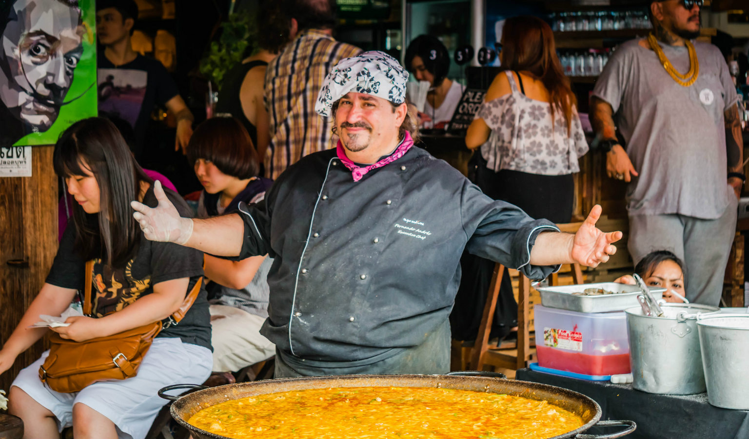 Dikke man met grote pan met eten op Chatucgak Market in Bangkok,
