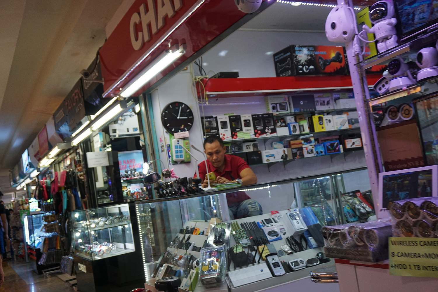 Man on his phone behind the counter at a little electronica shop in MBK Center