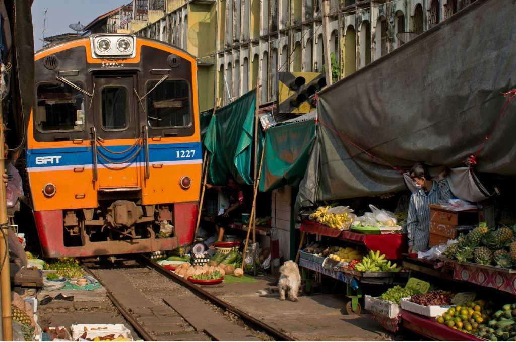 Trein rijdt dwars door de markt van de Maeklong Railway Market in Bangkok, Thailand