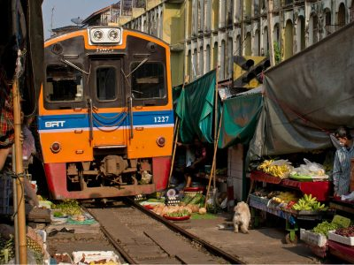 Train Passes Through The Maeklong Railway Market In Bangkok, Thailand