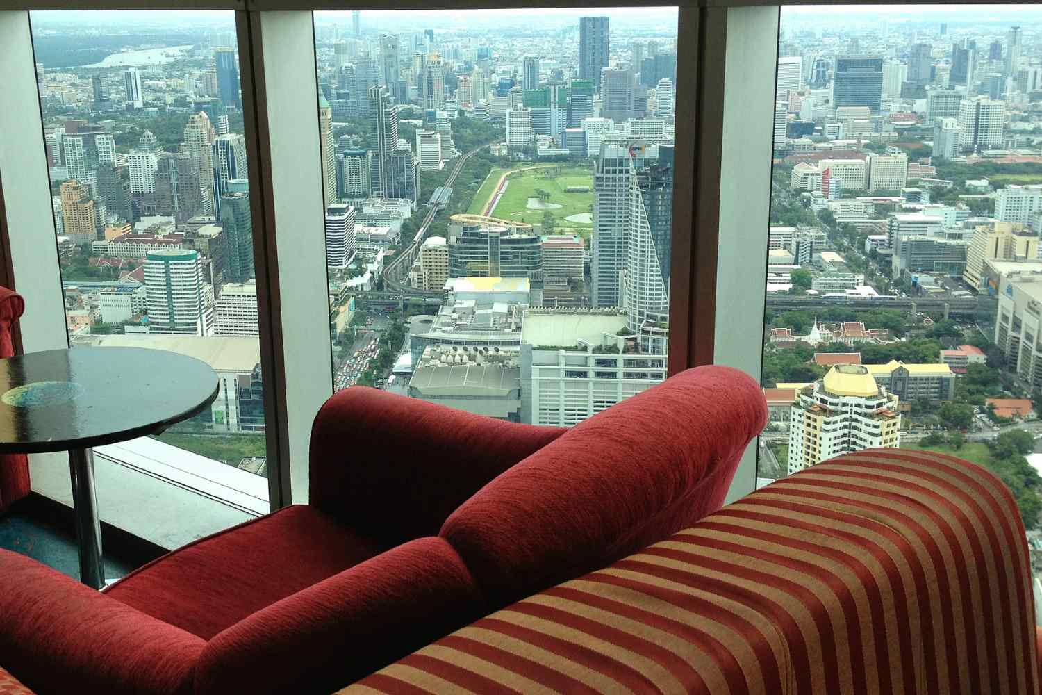 sitting area in the covered Baiyoke Sky Bar with large windows overlooking the city of Bangkok