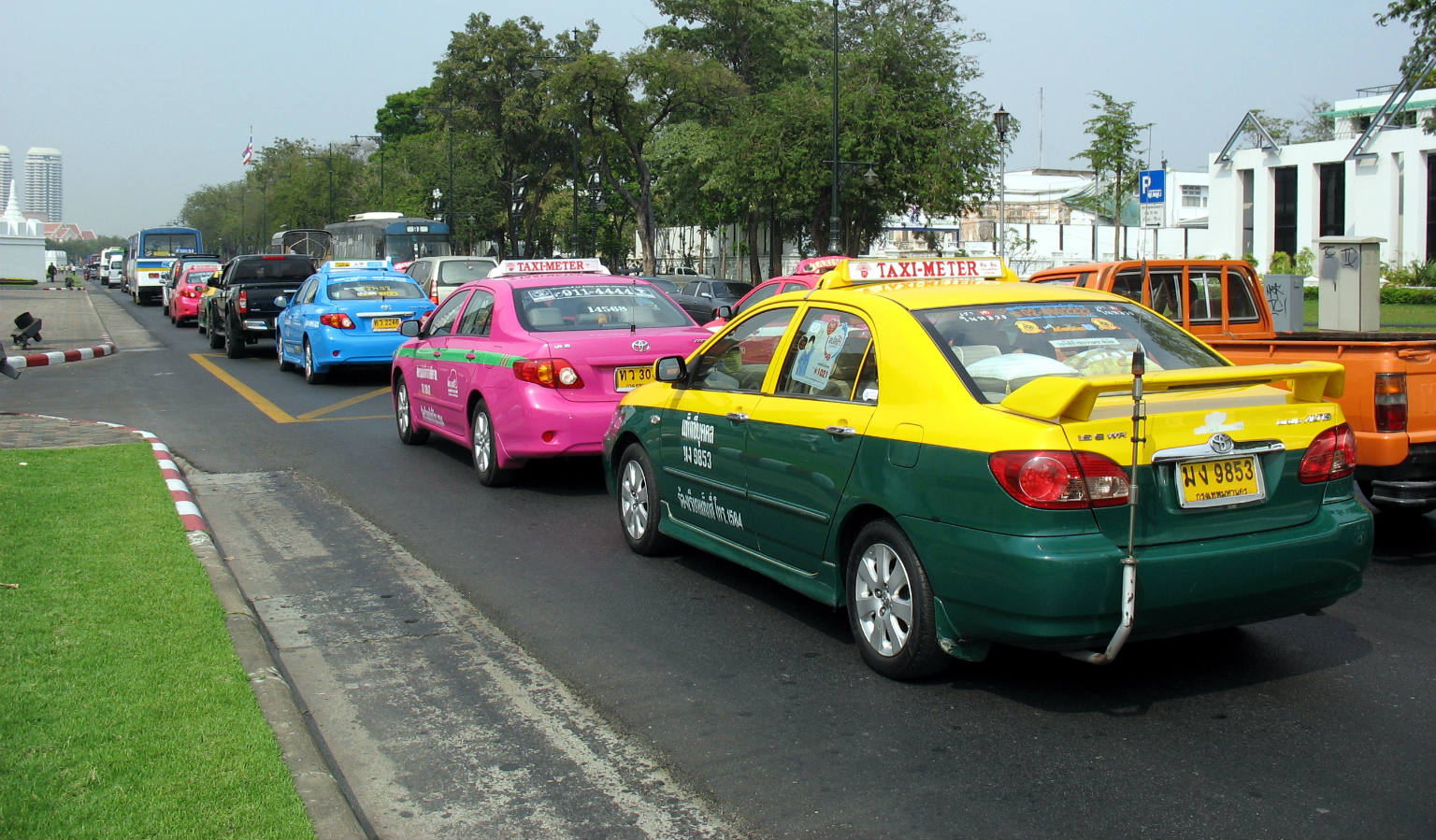 Groene, rose en blauwe taxi achter elkaar in de file