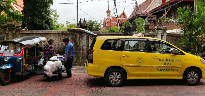 Taxichauffeur met gele taxi met open laadklep.