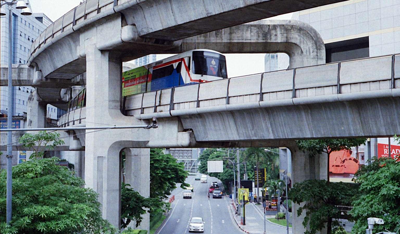 Betonnen pilaren boven de weg met skytrain die er overheen rijdt.