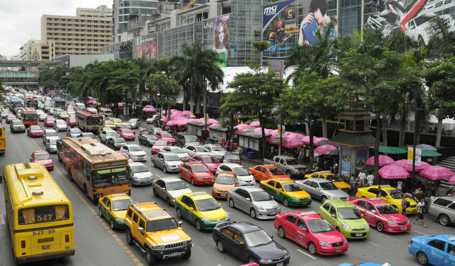 Personen auto's en gele, blauwe en groene taxi's in de file.