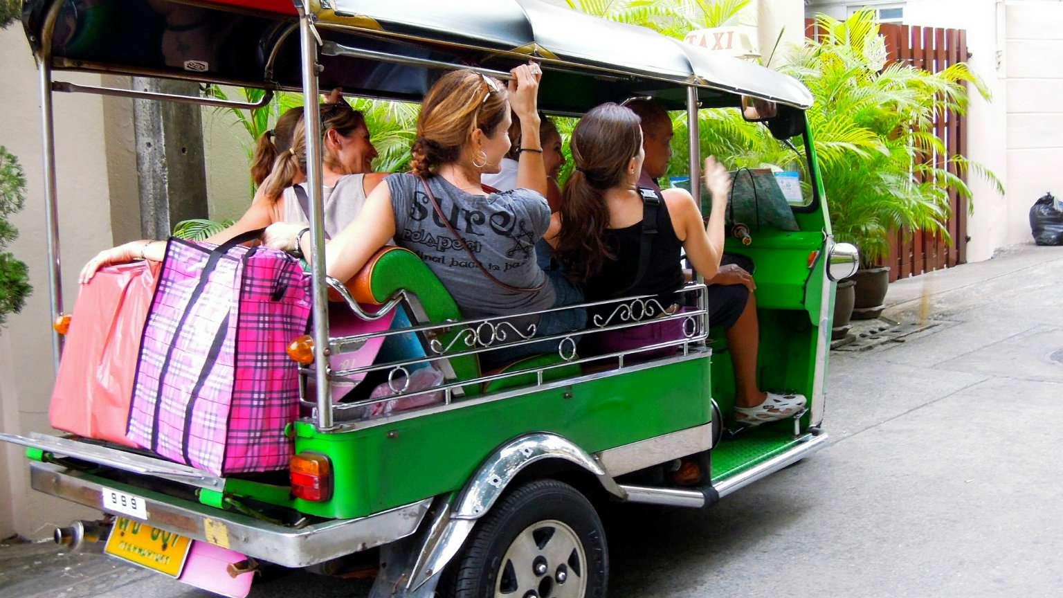 5 meiden met een Tuk Tuk bestuurder in één groene Tuk Tuk gepropt.