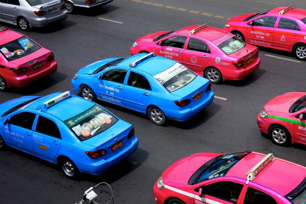 Pink and blue taxis at a bangkok street