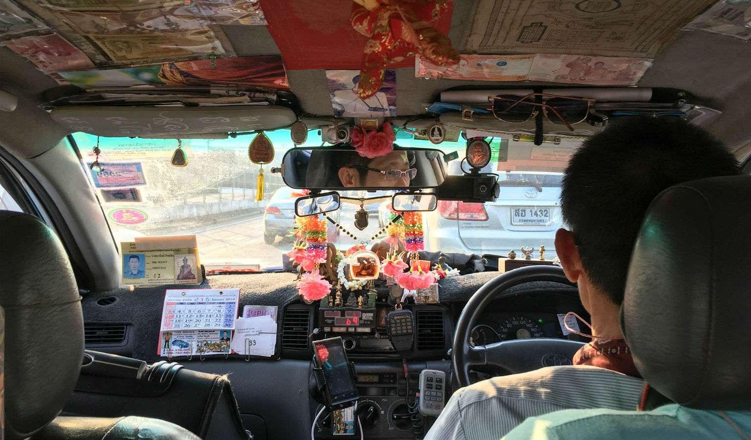Binnenkant van Taxi volgeplakt met brief geld en snuisterijen.
