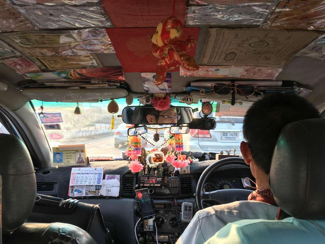 Binnenkant van Taxi in Bangkok volgeplakt met briefgeld en snuisterijen. Maar ook met de licentie en taxinummer erin.