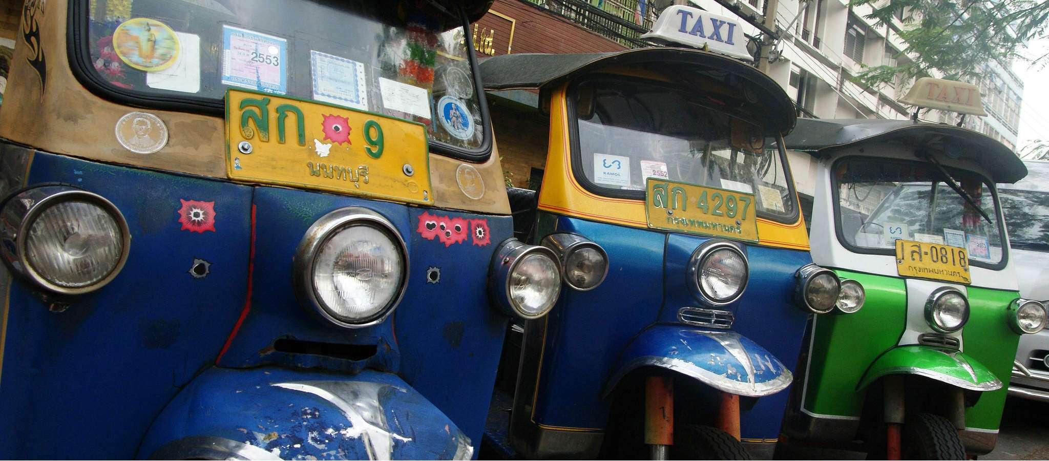 Drie Tuk Tuk's'op een rij in een straat in Bangkok, 2 blauw en 1 rode