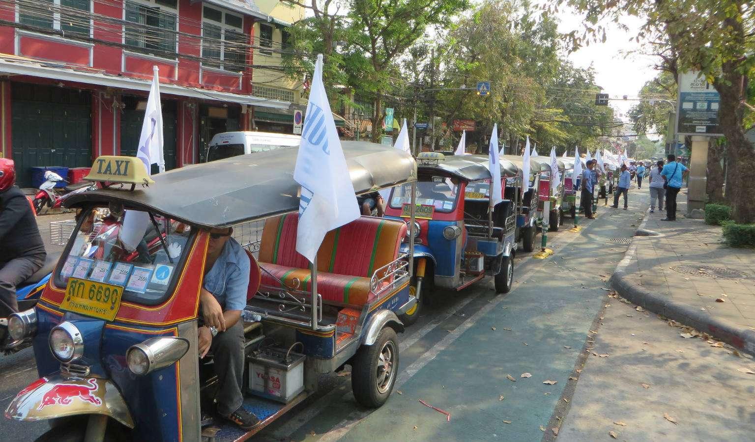 Een hele rij geparkeerde lege Tuk Tuk met bestuurder die wachten op klanten.