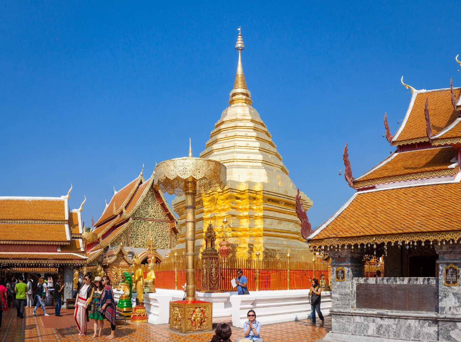 The golden temple of the Wat Phrathat Doi Suthep in Chiang Mai with a clear blue sky in the background.