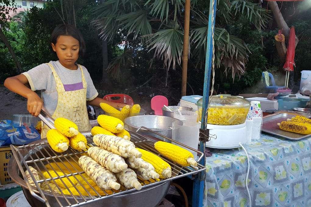 Meisje verkoopt maiskolven tijdens de Fisherman's Village Market van Bophut Beach in Thailand