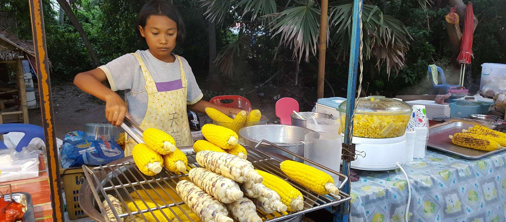 Meisje verkoopt maiskolven tijdens Fisherman's Village market van Bophut Beach.