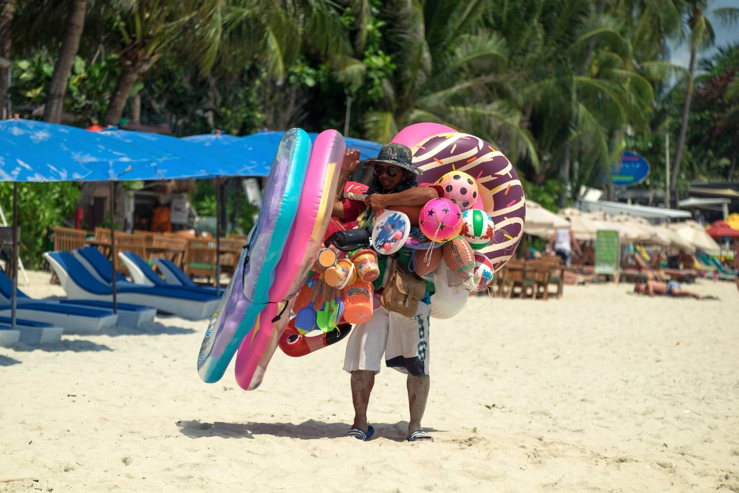 Vendor overloaded with swimming pools and air mattresses on Chaweng Beach