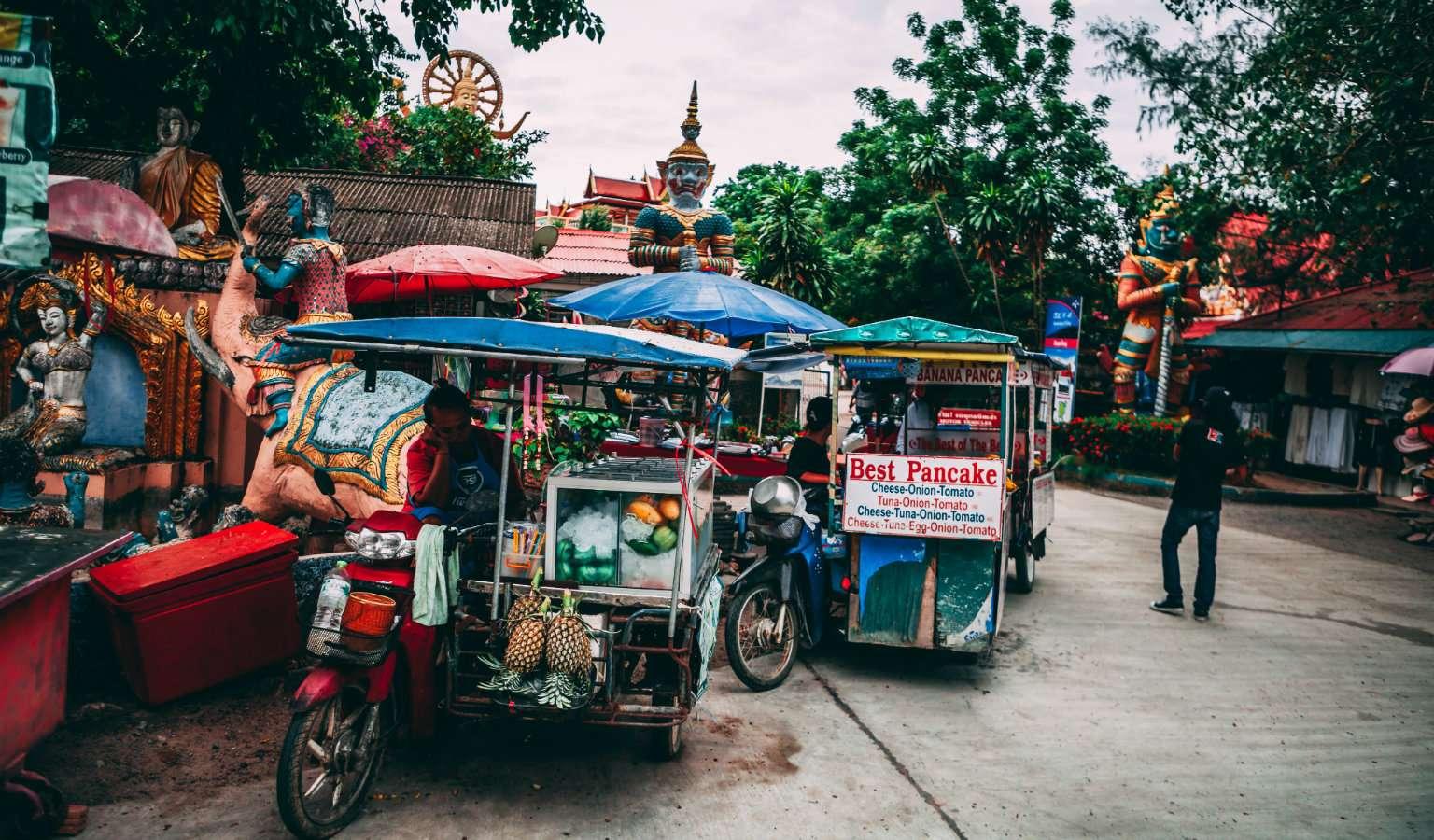 Kleine verrijdbare winkeltjes met Pad Thai en fruit bij de Markt van de Big Buddha