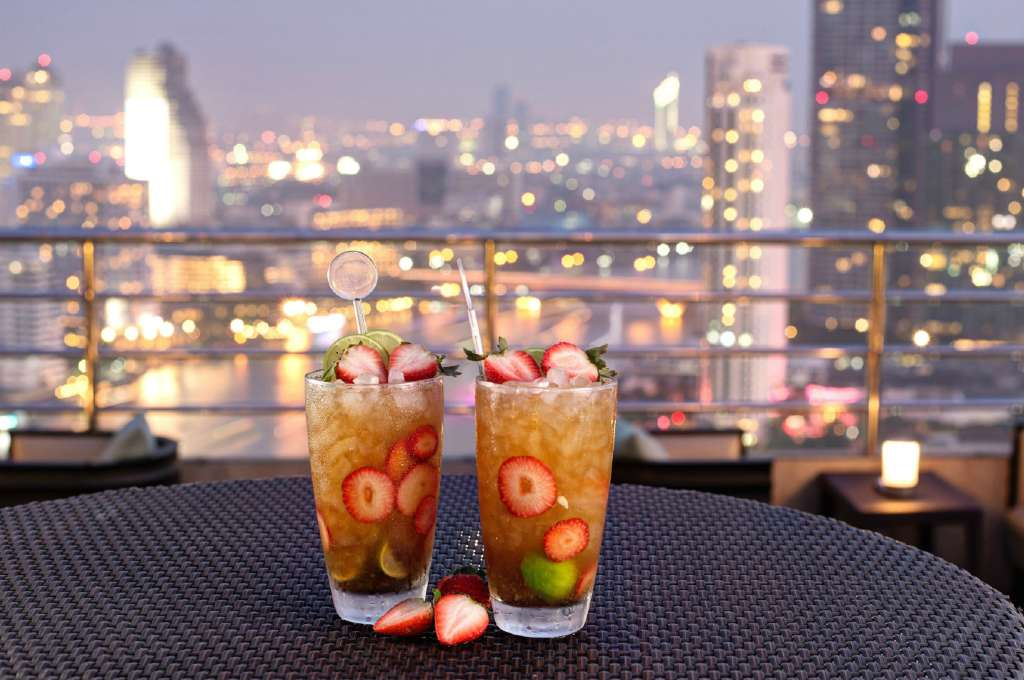 Two Cocktails with strawberry garnish on a table, with the skyline of Bangkok in the background.