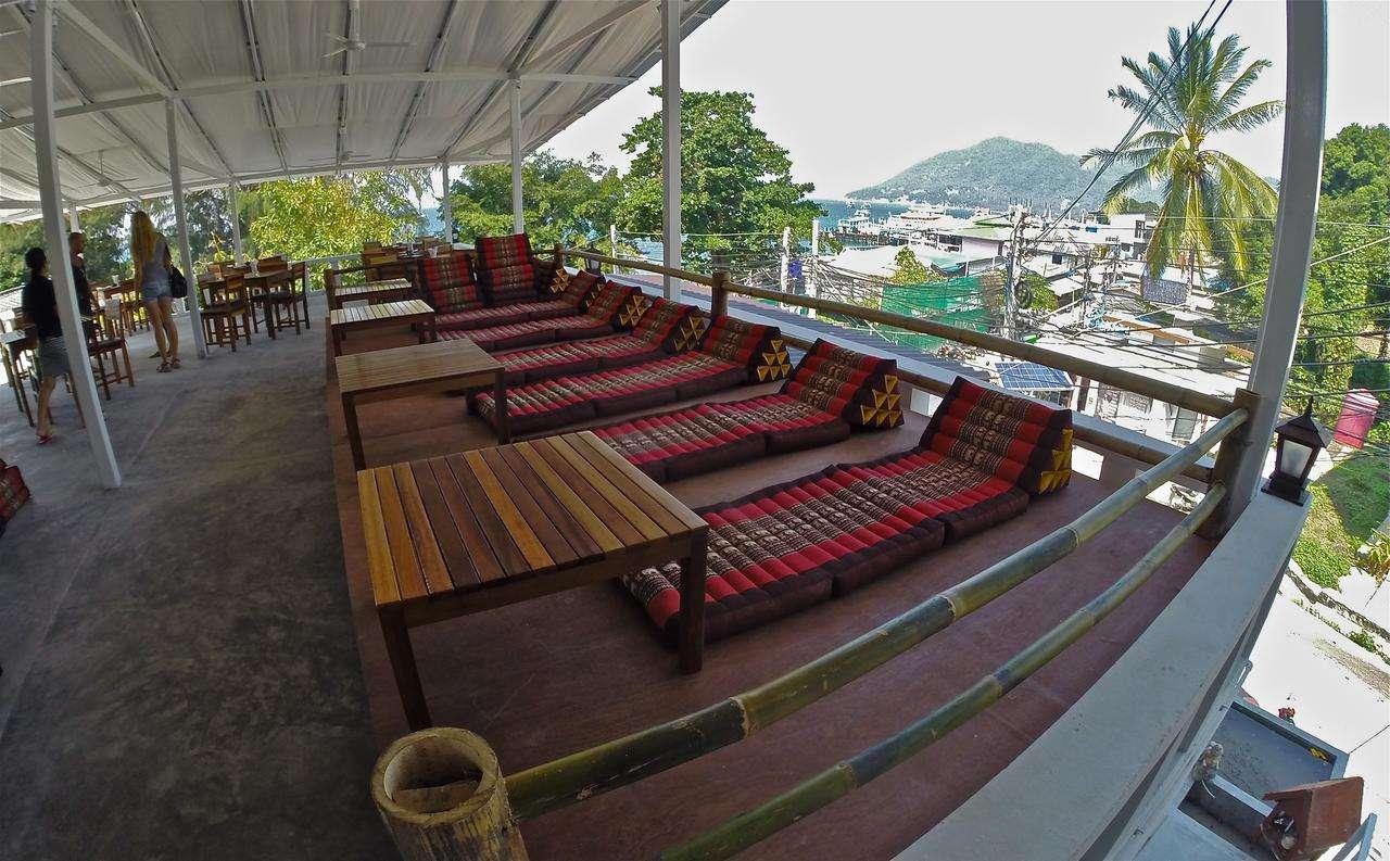 Terras van het Neptune Hotel met lig kussens en uitzicht over Ko Tao