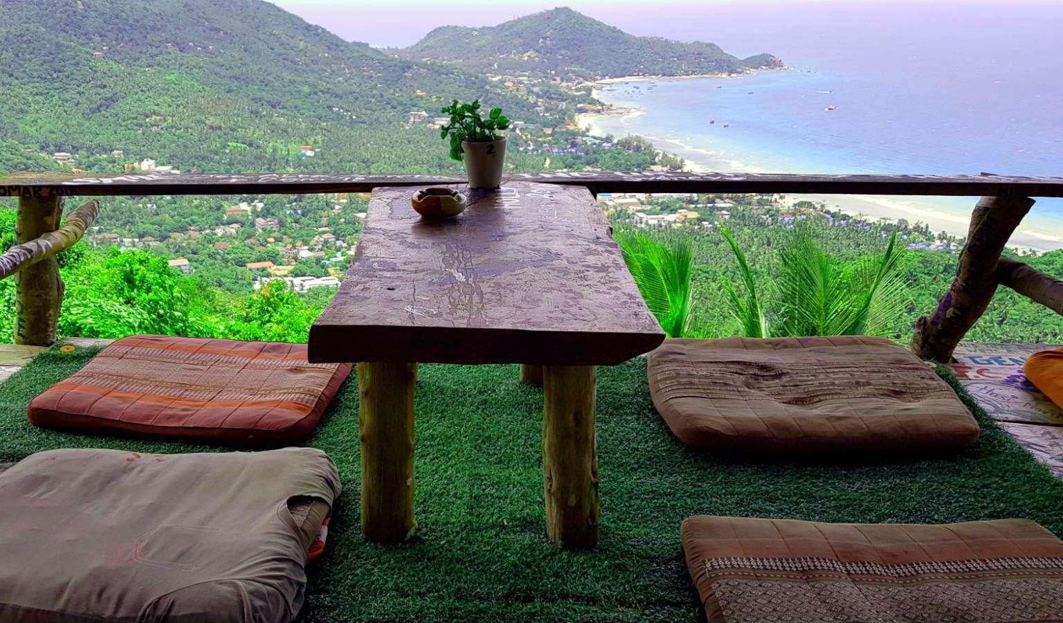 kussens rondom een tafeltje met uitzicht over Sairee Beach