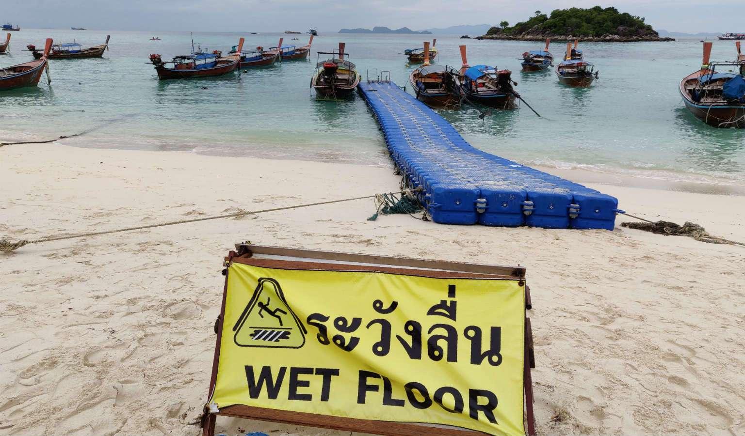 Wet floor sign for the floating pier on the Sunrise Beach