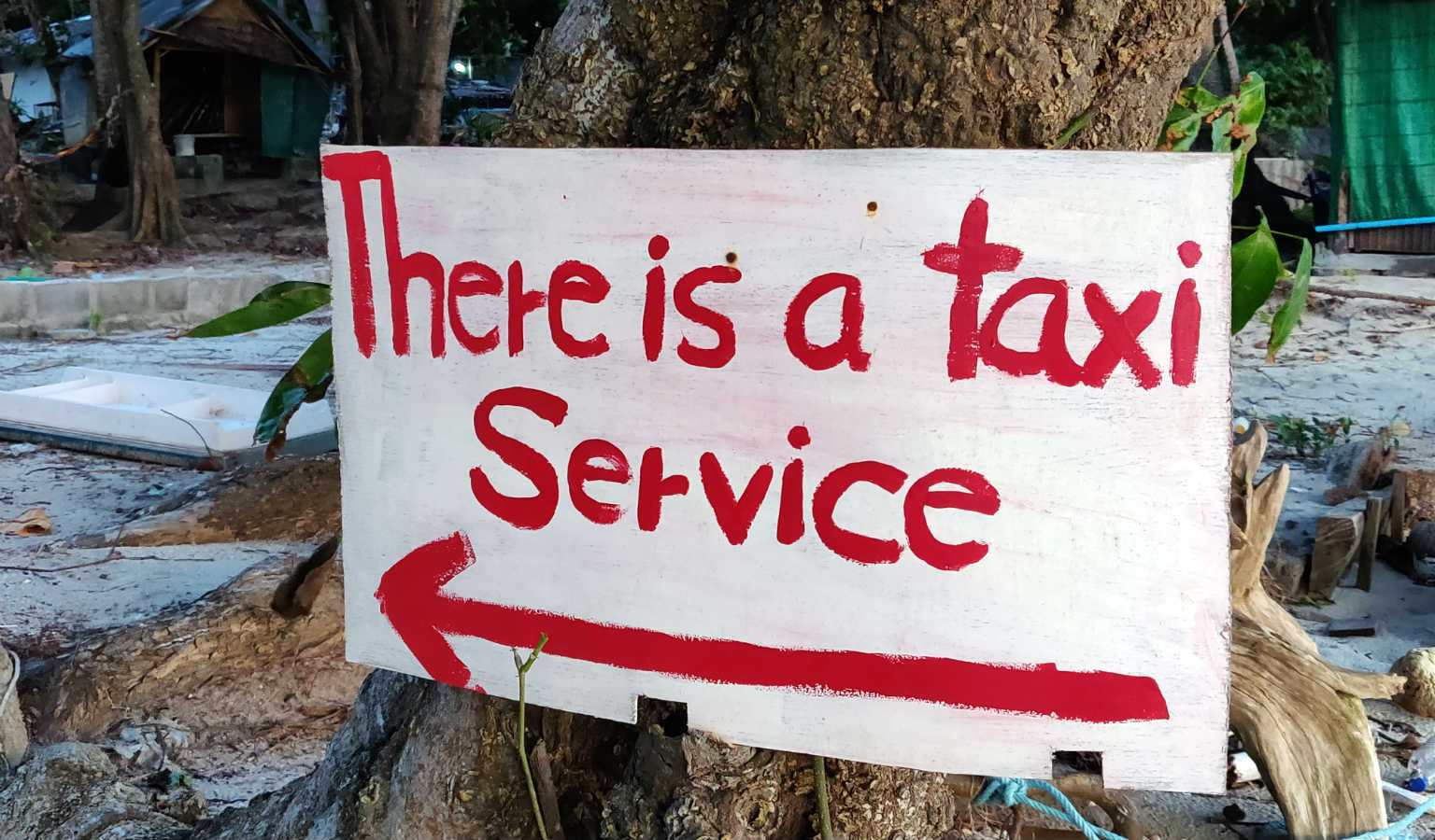 Bord met tekst there is a taxi service op Sunset Beach van Koh Lipe