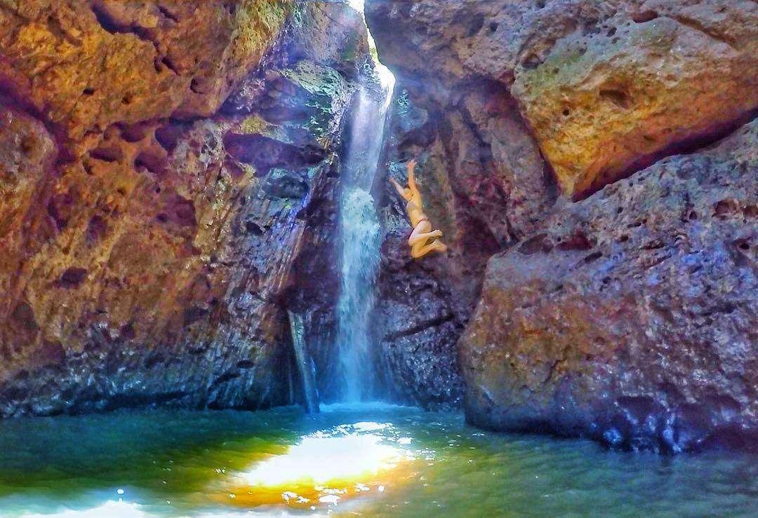 Meisje die springt in het bassin van de Pam Bok Waterfall in Pai