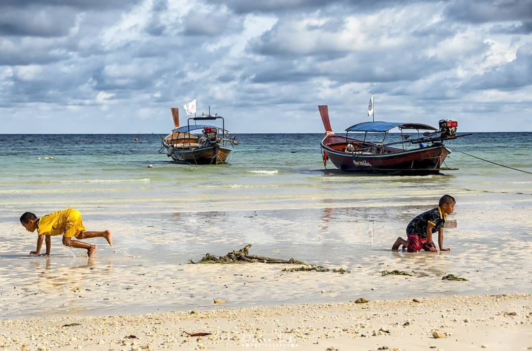 The beach and sea of Pattaya Beach on Koh Lipe with children playing in the foreground