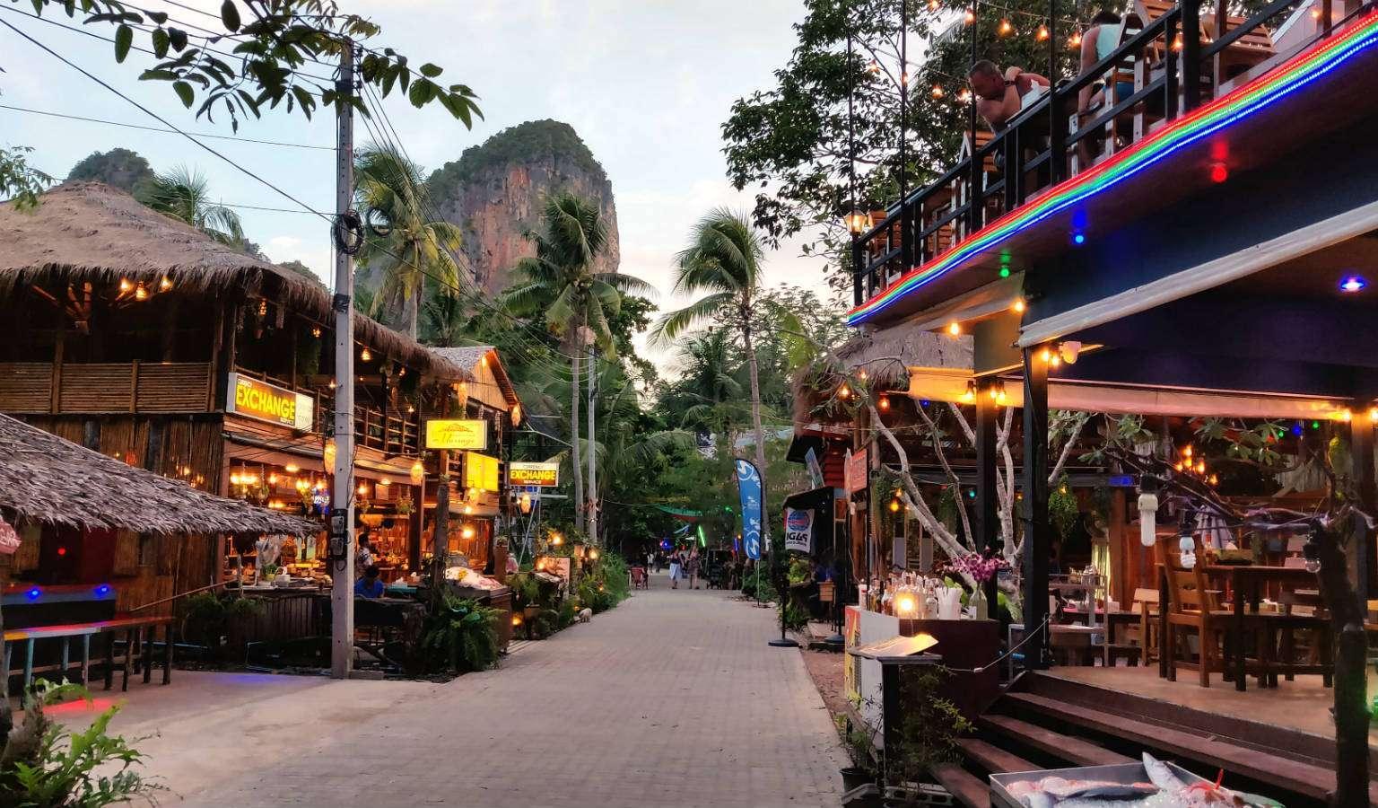 Restaurants aan walking street met op de achtergrond hoge rotsformatie