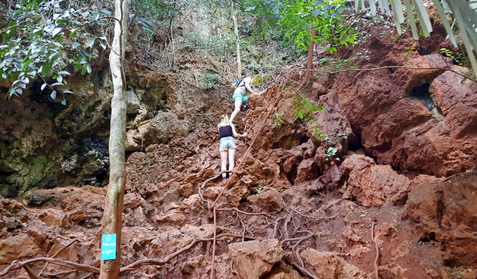 Jongen en meisje die tegen steile rots opklimmen naar Viewpoint van Krabi Railay