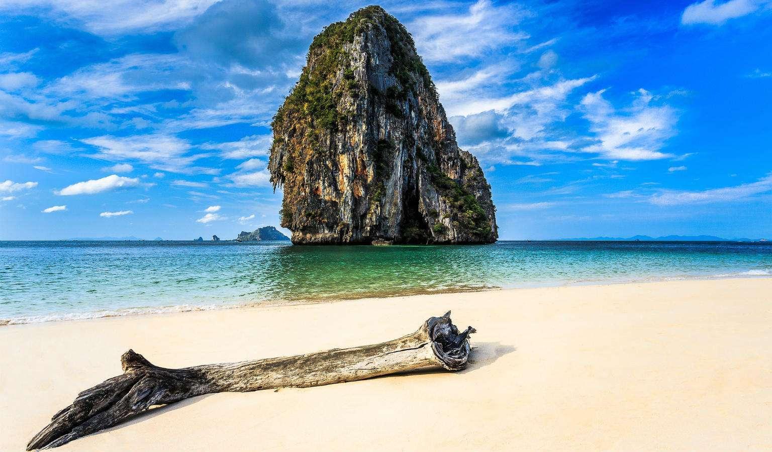 Grote rots in zee met aangespoeld hout op het strand van Ao Phra Nang Beach