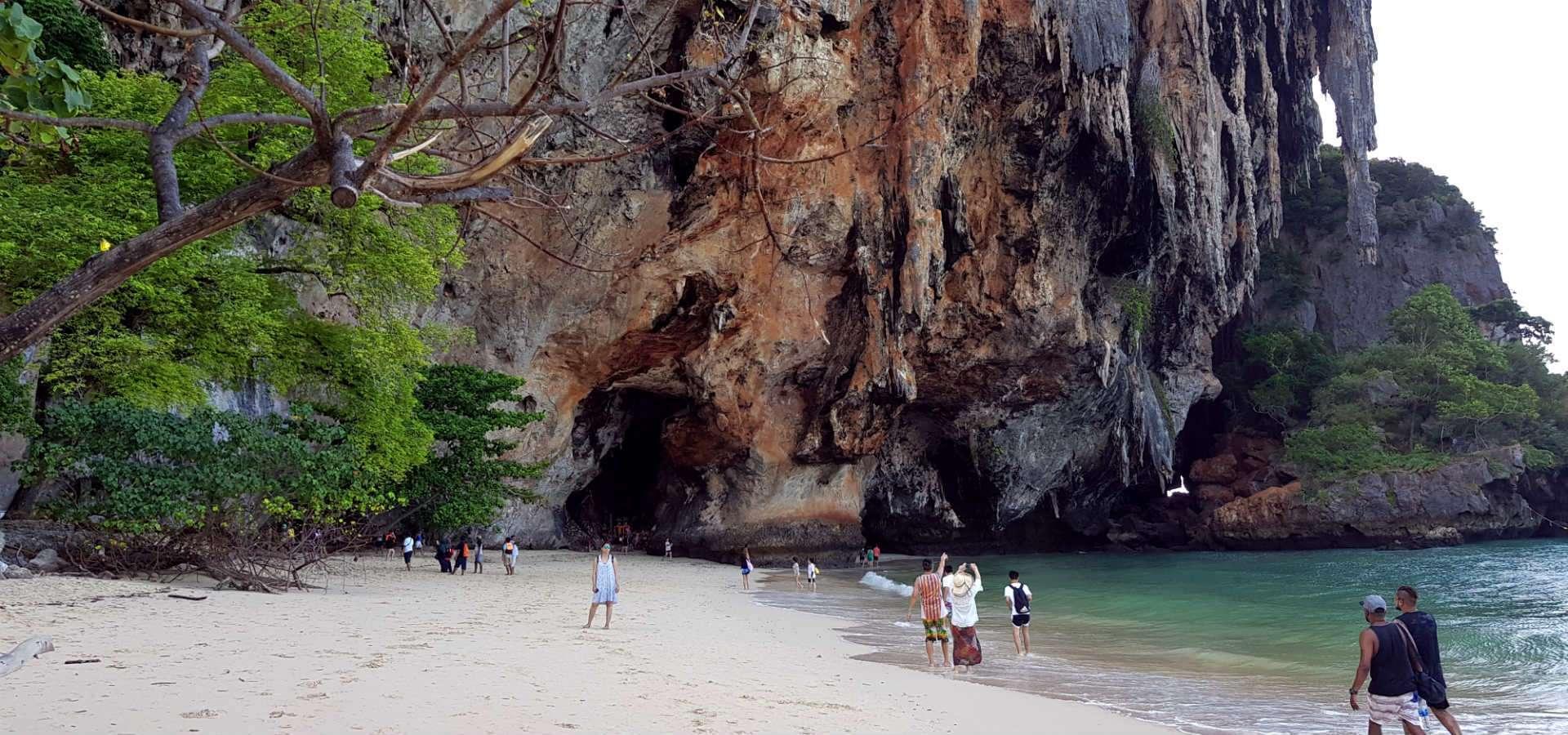 Strand met hoge rotswanden die doorlopen in blauwe zee.