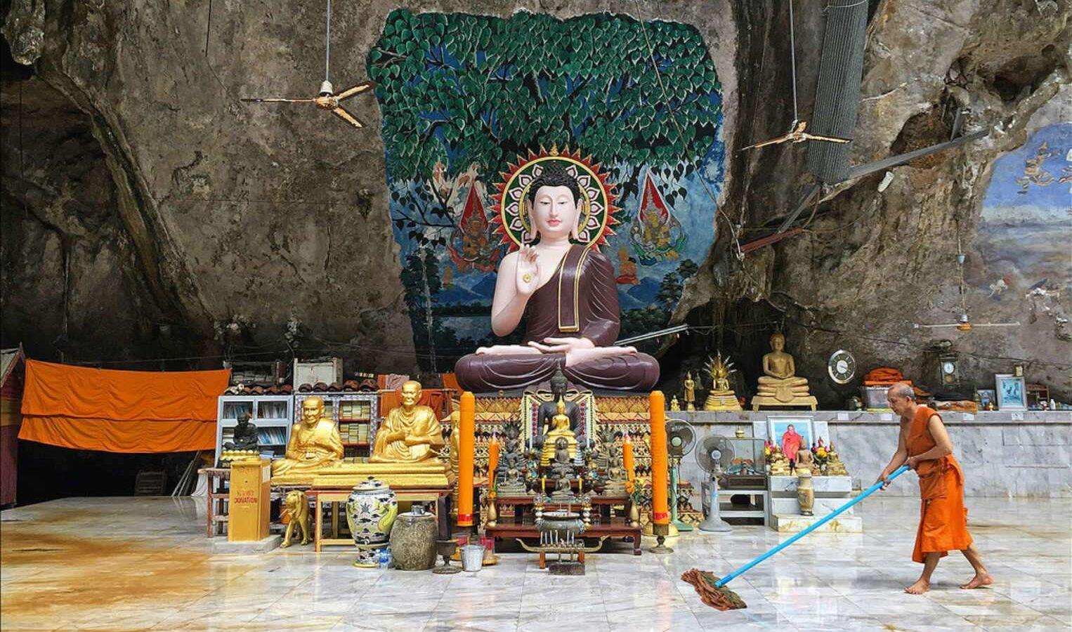 Tempel in grot bij Wonderland met een monnik die de vloer dweilt.