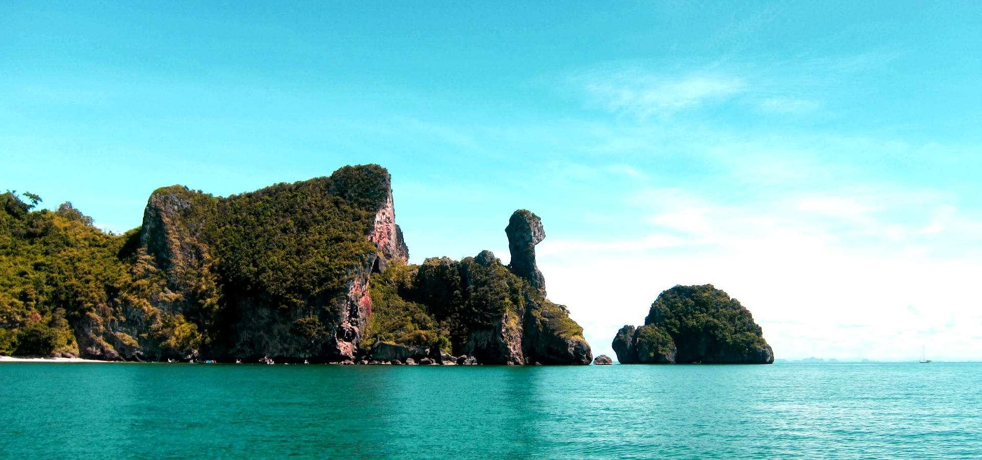 Rotsen/ karstgebergte in een blauwe zee bij Krabi