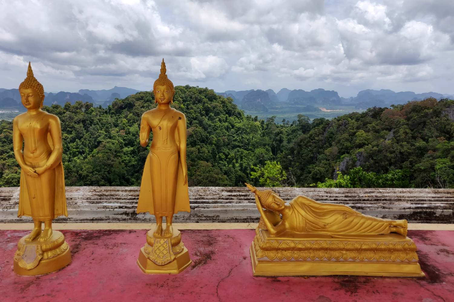 Little golden Buddhas at the Tiger Temple with a view over Krabi and the sea in the background.