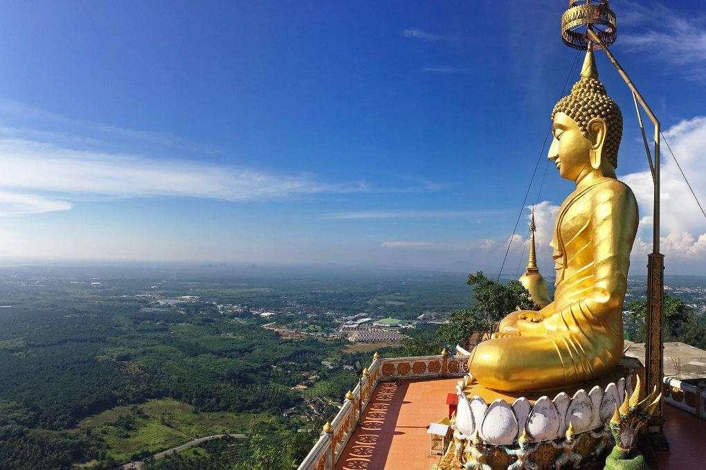Grote goudkleurige Boeddha boven op een berg., met 360 graden uitzicht over Krabi.