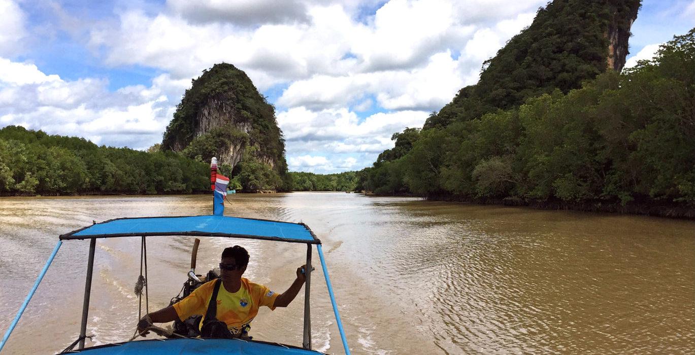 Longtailboot met bestuurder op de bruine rivier