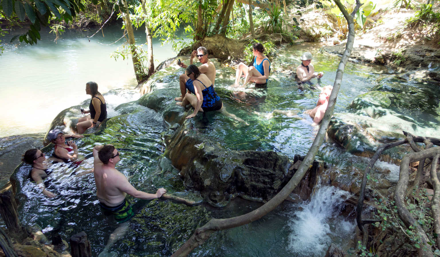 People enjoy the warm water of the Namtok Ron Hot Springs in Krabi