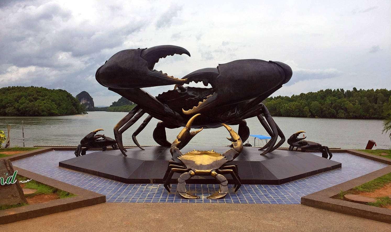 Beeld van een grote krab met gouden accenten langs de rivier
