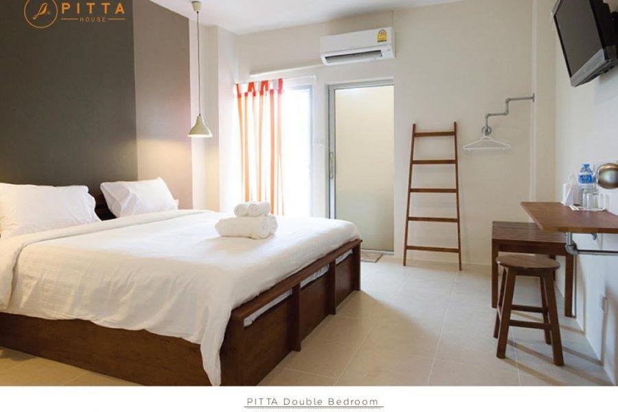 hotelkamer pita house, met fris witte inrichting en hout accenten.