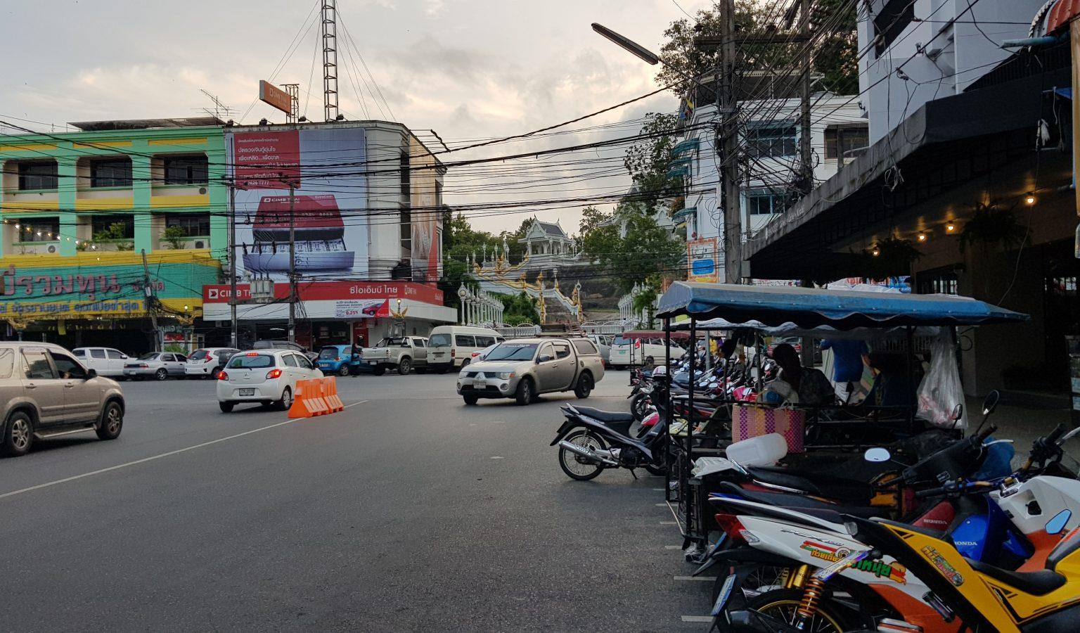 Straatbeeld met scooters en auto's met een witte tempel op de achtergrond.