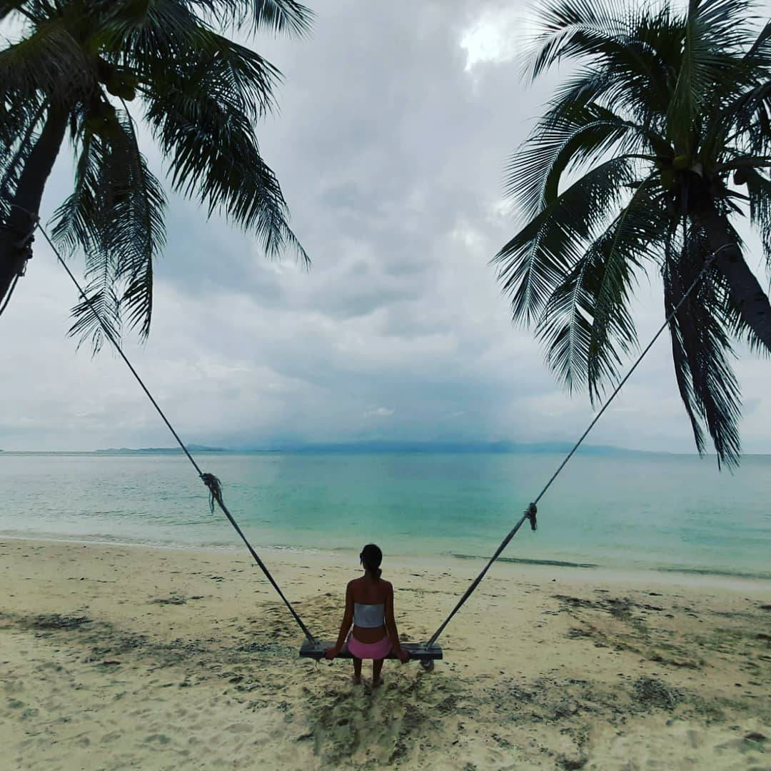 A swing between two palm trees on Leela Beach, Koh Phangan in Thailand