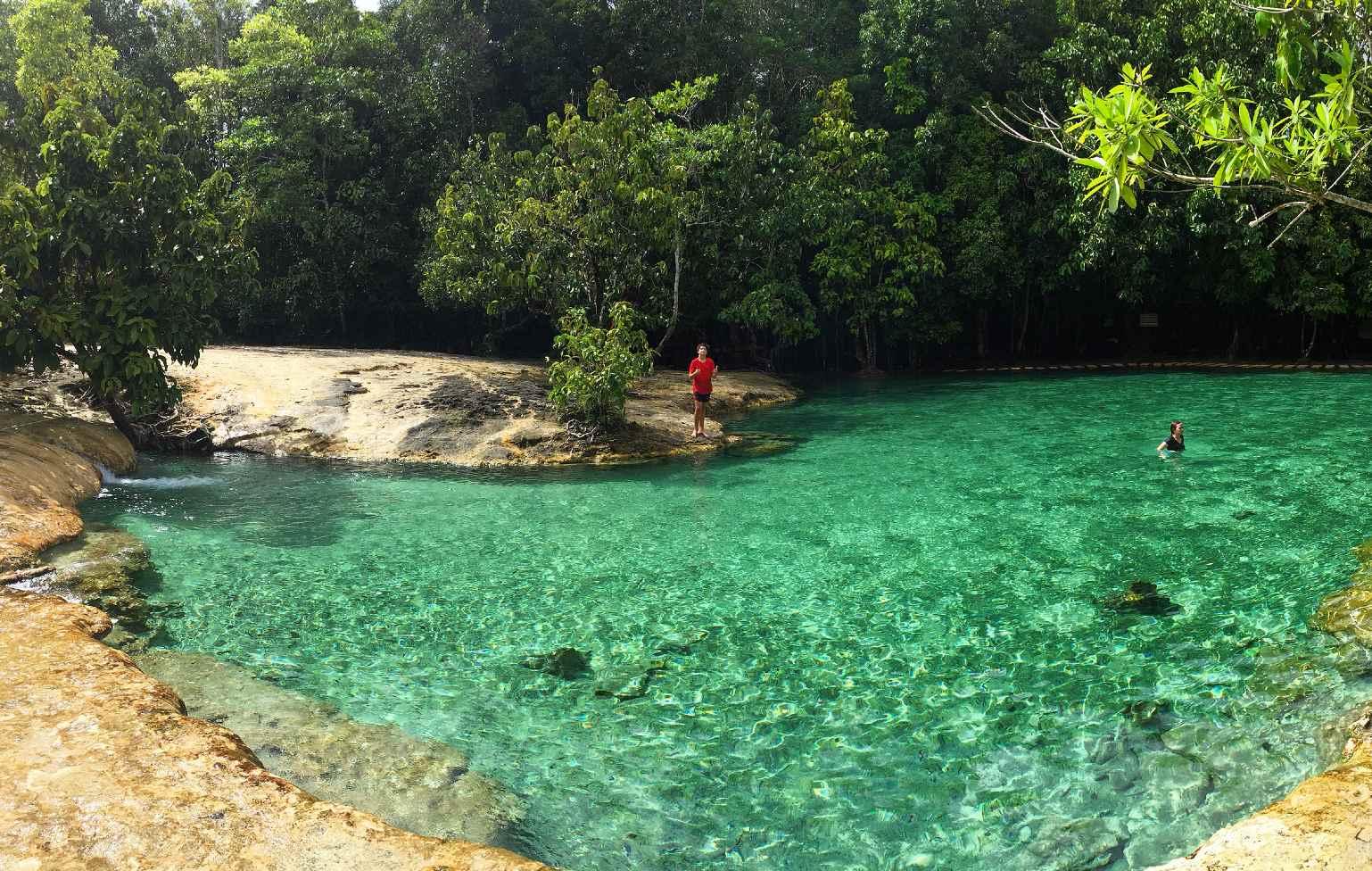 Smaragdgroene water van de Emerald Pool omringd met rotsen en jungle, Krabi