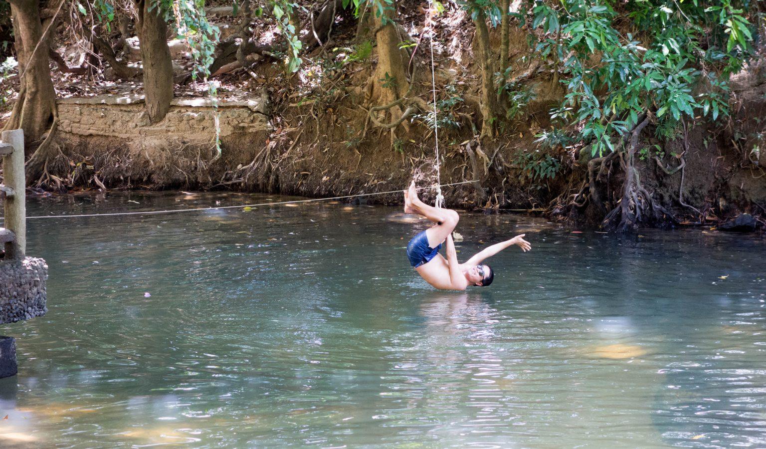 Jongen zwaait aan een touw de rivier in bij de Namtok Ron Hot Spring in Krabi